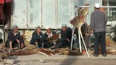 Men are selling brooms at the Kashgar Sunday Bazaar Stock Footage
