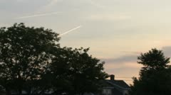 Plane landing over house and trees at sunset Stock Footage