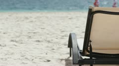 Lounge chair with people on beach Stock Footage