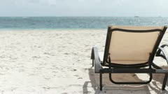 Lounge chair on beach with ocean Stock Footage