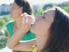 Female friends talking and drinking vodka shots on terrace NTSC Stock Footage