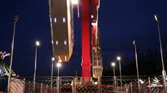 Night time at carnival with spinning ride Stock Footage