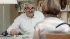 Senior man reading newspaper with wife in recreation center Stock Footage