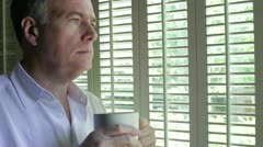 Man thinking with coffee while looking out a window Stock Footage