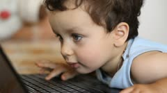 Young boy looking at a lap top screen Stock Footage