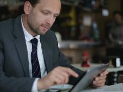 Businessman working on tablet computer in the cafe, steadicam shot NTSC Stock Footage