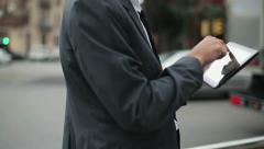 Businessman working on tablet computer by the street, steadicam shot HD Stock Footage