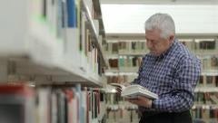 Happy old man reading and choosing book in library Stock Footage