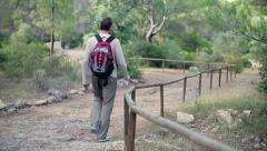 Man with backpack walking in the park HD Stock Footage