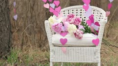 Decorations: White wicker Chair and a garland of paper hearts Stock Footage