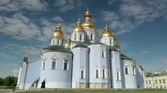Two monks passing by the Temple of Mikhailovsky in Kiev, Ukraine Stock Footage