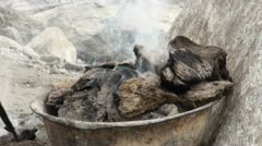 Poking burning manure near a traditional yurt Stock Footage