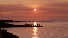 Beautiful fiery red sunset/sunrise over a picturesque scene of a dock Stock Footage