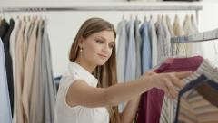 Beautiful young woman choosing shirt in clothes shop Stock Footage