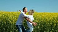 Happy couple on rape field Stock Footage