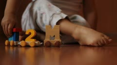 A child dressed in white playing with wooden toys on the floor Stock Footage