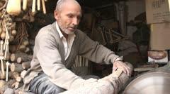 Old Uyghur man cuts large chunks of wood Stock Footage