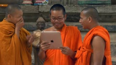 siem reap cambodia young boy monks laughing and having fun at apple ipad comp - stock footage