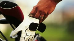 Golfer putting on his glove. - stock footage