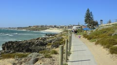 Perth Australias beautiful shoreline and rocks with waves and mother walking - stock footage