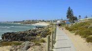 Perth Australias beautiful shoreline and rocks with waves and mother walking Stock Footage
