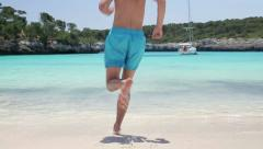 Man in swimming trunks running to the sea, slow motion HD Stock Footage