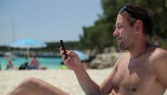 Young man using cellphone on the beach, dolly shot HD Stock Footage