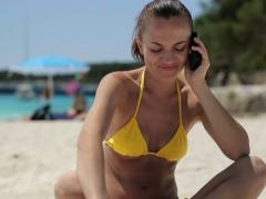 Young woman talking on cellphone on public beach, dolly shot NTSC Stock Footage
