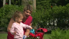Mother watering flowers with her daughter Stock Footage