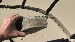 Holding a piece of cracked earth symbolizing climate change effects Stock Footage