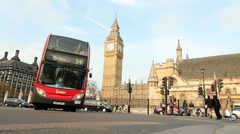 Street level shot of Big Ben as a red Double decker bus drives by Stock Footage