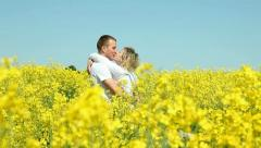 Sweet couple in a field of rape Stock Footage
