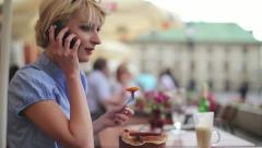 Businesswoman receiving phone call while eating lunch, steadicam shot HD Stock Footage