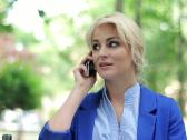 Attractive businesswoman talking on cellphone in the park, steadicam shot NTSC Stock Footage