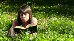 Beautiful girl reading a book in forest on flowers field Stock Footage