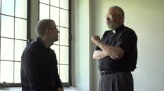 Priest talking with parishioner in a church Stock Footage