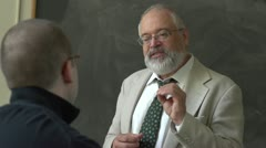 Professor and student talking in a classroom Stock Footage