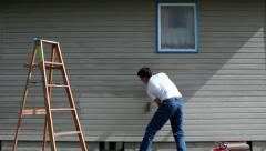 Man Repainting House Wall - stock footage