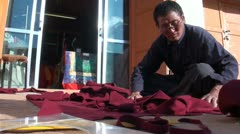 A tailor is making robes for monks in a Tibetan village Stock Footage