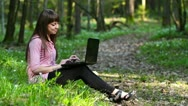 Stock Video Footage of beautiful girl with a laptop in the forest