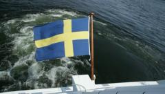 Swedish flag blows in wind on boat in Stockholm archipelago. Stock Footage