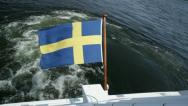 Stock Video Footage of Swedish flag blows in wind on boat in Stockholm archipelago.