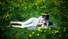 Teenager girl lying on meadow full of sow-thistle and writing letter Stock Footage