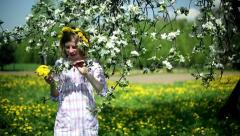 Young girl smelling flowers in the orchard, dolly shot Stock Footage