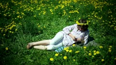 Teenager girl lying on meadow full of sow-thistle with cellphone Stock Footage