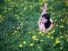 Happy woman lying on meadow full of sow-thistle Stock Footage