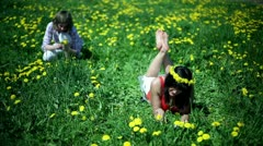 Mother with daughter reading a book on meadow full of sow-thistle Stock Footage
