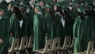 Stock Video Footage of Stock Footage - High School Graduates march into stadium - Green Gowns
