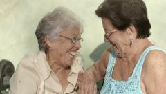 Old friends, two happy senior women talking in park - stock footage