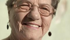 Elderly woman with glasses smiling and looking at camera - stock footage